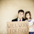 "Grungy, color photo of an unemployed young businessman in a suit and tie with his daughter on the street holding a cardboard sign reading ""WILL WORK FOR FOOD""."